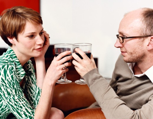 Stock Photo: 1527R-1078615 Couple Looking Into Each Other's Eyes and Toasting With Red Wine