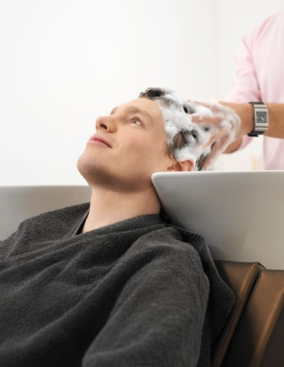 Stock Photo: 1527R-1078824 Man Sitting at a Sink Having His Hair Washed by a Hairdresser