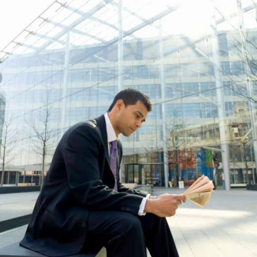 Stock Photo: 1527R-1078923 Businessman Sits on a Bench Reading a Newspaper