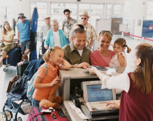 Stock Photo: 1527R-1079117 Family With Two Young Children Checks in at an Airport