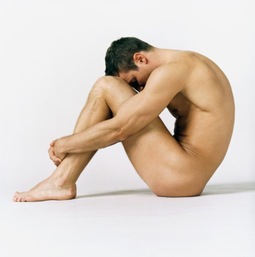 Stock Photo: 1527R-1079174 Naked Man Sitting With His Hands Around His Knees