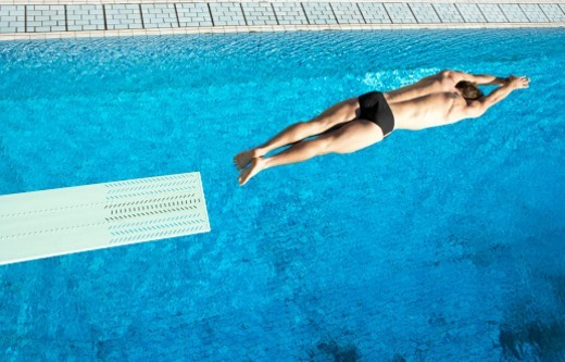 Man Diving Into a Swimming Pool From a Board : Stock Photo