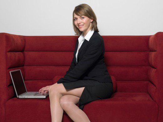 Businesswoman Sitting on a Sofa With a Laptop : Stock Photo