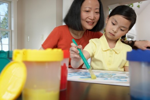 Woman Sits With Her Young Daughter at a Table at Home, Helping Her to Paint a Picture : Stock Photo