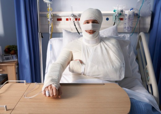 Man Lying in a Hospital Bed, Covered in Bandages : Stock Photo