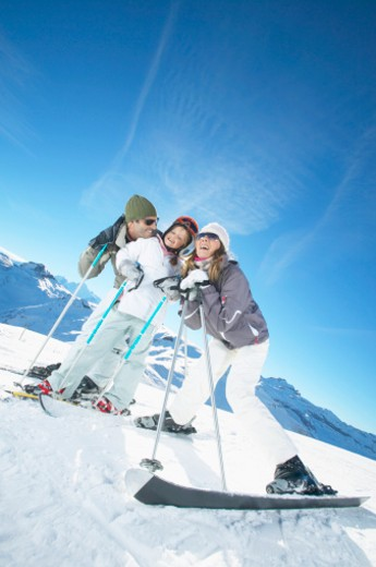 Stock Photo: 1527R-1080497 Man and Woman Stand on a Ski Slope With Their Young Daughter