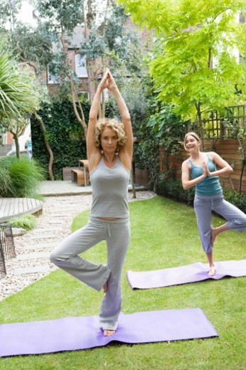 Stock Photo: 1527R-1080930 Mother and daughter (13-15) performing yoga in garden