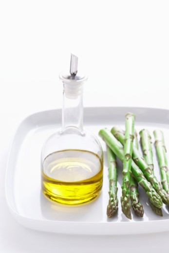 Stock Photo: 1527R-1081137 Asparagus and olive oil on plate, close-up