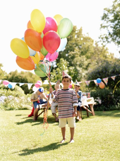 Boy (5-7) holding bunch of balloons outdoors, friends in background : Stock Photo