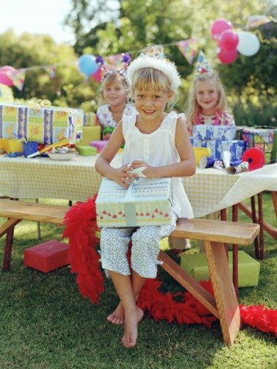 Girl (5-7) opening present at table by friends outdoors : Stock Photo