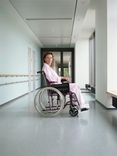Woman in wheelchair in hospital corridor, portrait : Stock Photo
