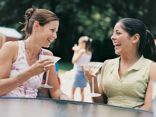 Two Women Sitting Outdoors in a Garden Enjoying Cocktails : Stock Photo