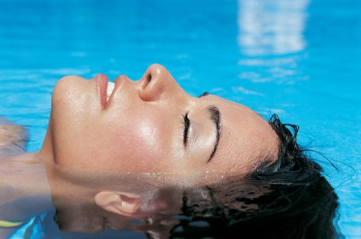 Stock Photo: 1527R-1082279 Side View of a Young Woman Floating in a Swimming Pool With Her Eyes Closed