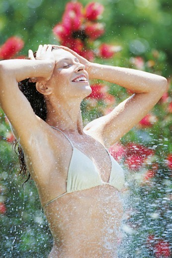 Side View of a Young Woman in a Bikini top Being Splashed With Water : Stock Photo