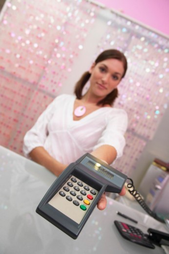 Young female shop assistant holding out chip and PIN machine, close-up : Stock Photo