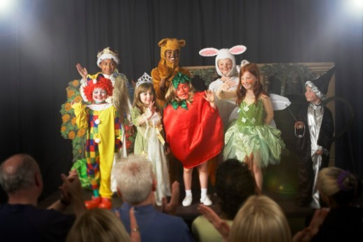 Stock Photo: 1527R-1082939 Group of children (11-14) wearing costumes, waving on stage