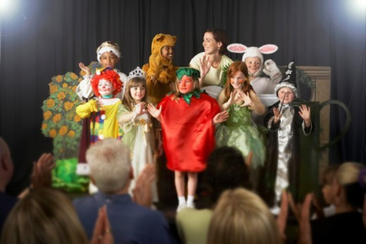Children (4-9) wearing costumes and teacher waving on stage : Stock Photo