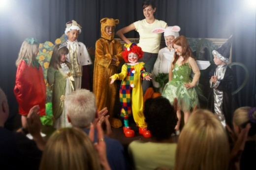Group of children (4-9) wearing costumes and teacher on stage : Stock Photo
