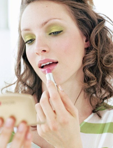 Young woman applying lipstick in compact mirror, close-up : Stock Photo