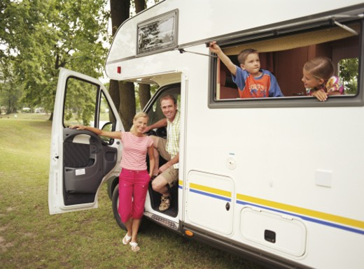 Parents and children (8-11) in motorhome, smiling, portrait of parents : Stock Photo