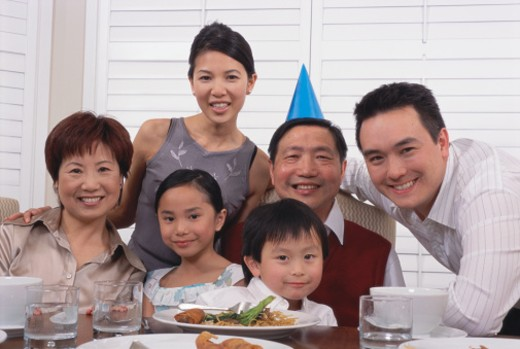 Three generational family gathered by dinner table, smiling, portrait : Stock Photo