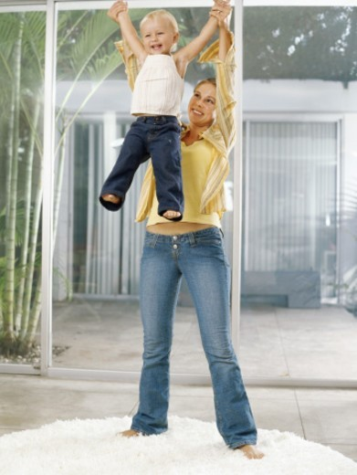 Stock Photo: 1527R-1085438 Woman lifting female toddler (21-24 months) above head, smiling