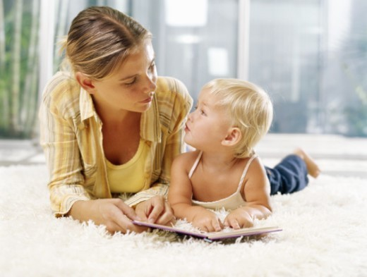 Stock Photo: 1527R-1085443 Woman and female toddler (21-24 months) lying on rug with book, looking at each other
