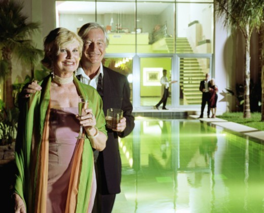 Senior couple standing by pool, holding drinks, smiling, portrait : Stock Photo