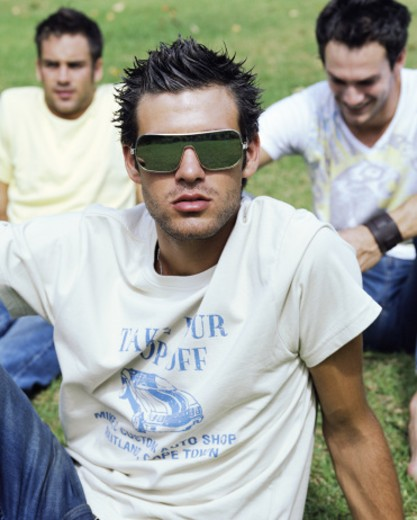 Three young men relaxing outdoors, one wearing sunglasses, portrait : Stock Photo