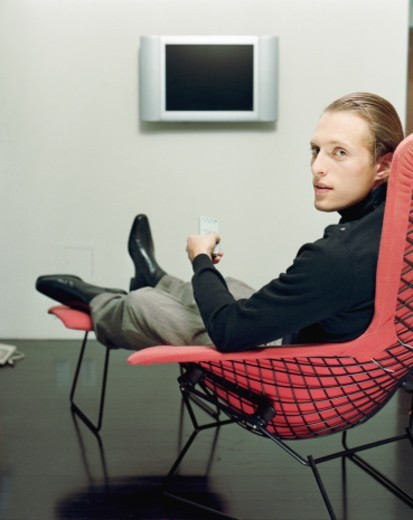 Young man sitting in modern chair, holding remote control, portrait : Stock Photo