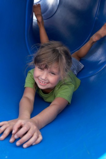 Stock Photo: 1527R-1087584 Girl (5-7) lying in tubular slide, smiling, portrait
