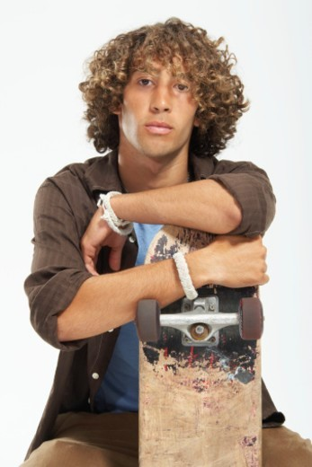 Teenage boy (16-18) with curly hair, leaning on skateboard, portrait : Stock Photo