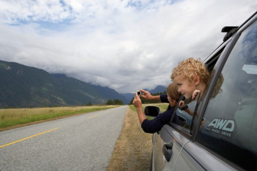 Son (5-7 years) leaning out of rear window. : Stock Photo