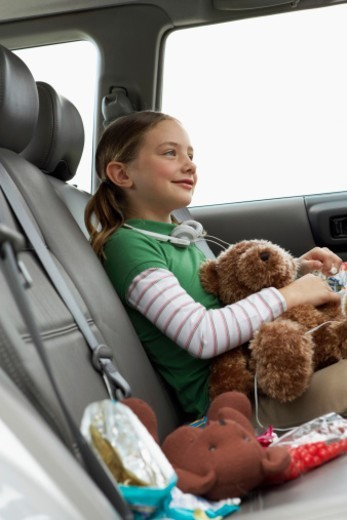 Stock Photo: 1527R-1088100 Girl (6-8 years) sitting with soft toys on rear seat of car, smiling, side view