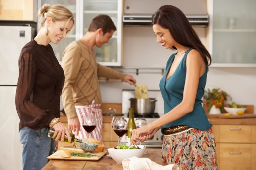 Two women and man preparing food in kitchen, smiling : Stock Photo