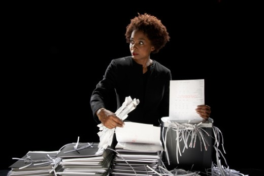 Businesswoman shredding documents looking to one side : Stock Photo