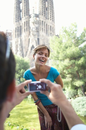 Spain, Barcelona, man photographing woman by Sagrada Familia : Stock Photo