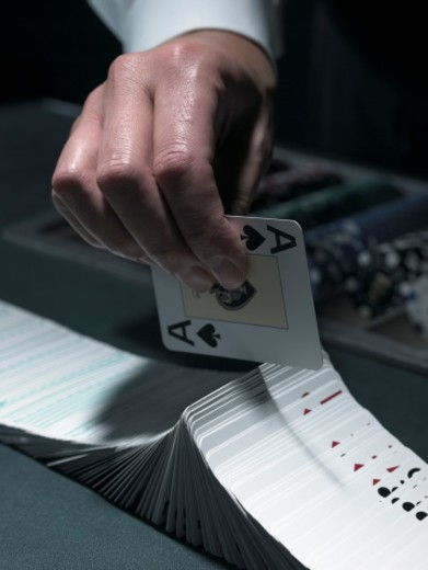 Male croupier extravagantly shuffling cards at table, close-up : Stock Photo