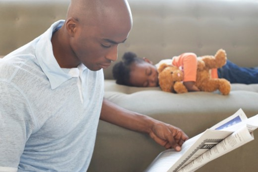 Father reading newspaper by daughter (2-4) asleep on sofa : Stock Photo