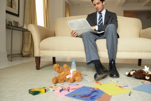 Stock Photo: 1527R-1089928 Businessman reading newspaper by soft toys and crayons, low angle view