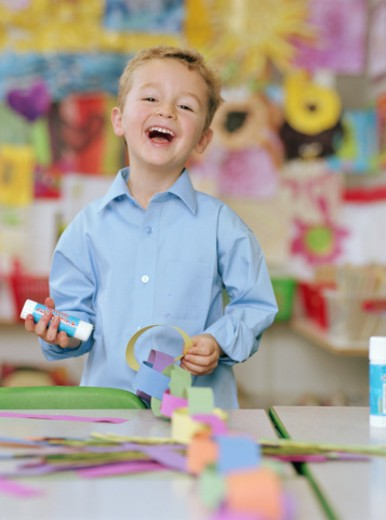 Schoolboy (4-6) making paper chain at table, laughing, portrait : Stock Photo