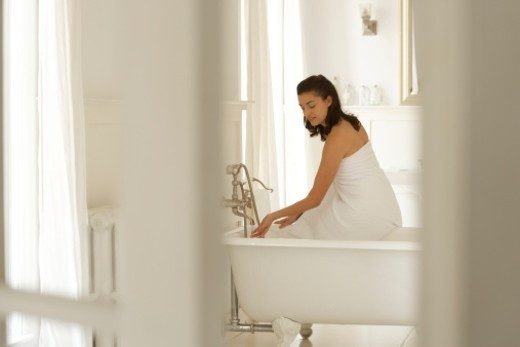 Young woman sitting on edge of bath, testing water with hand : Stock Photo