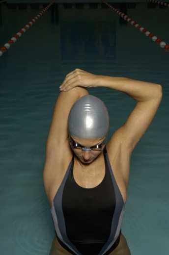 Female swimmer, stretching arms in swimming pool : Stock Photo