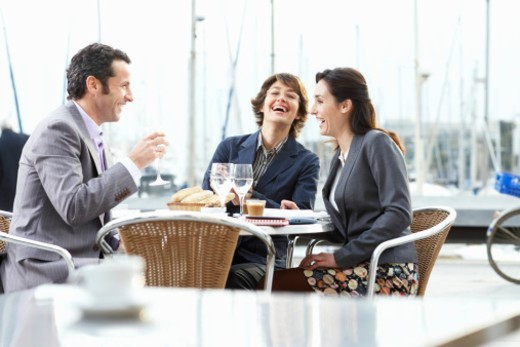 Three businesspeople sat at table outdoors, smiling : Stock Photo
