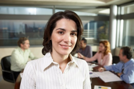 Stock Photo: 1527R-1092307 Young businesswoman in meeting room with colleagues, smiling, portrait