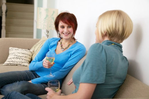 Two young women relaxing on sofa, holding wine glasses : Stock Photo