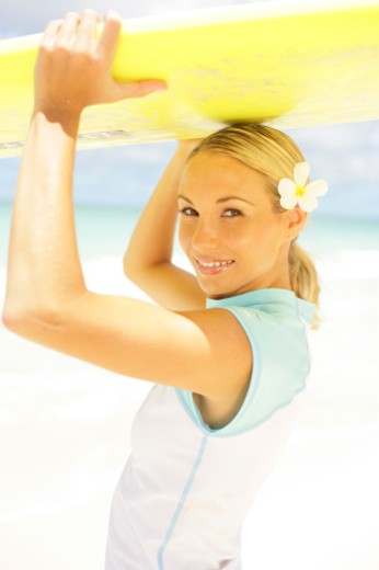 Young woman holding surfboard on head, smiling, portrait : Stock Photo