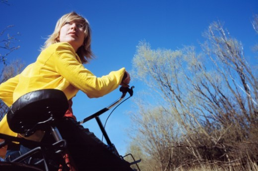 Woman riding bicycle outdoors, low angle view : Stock Photo