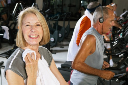 Senior woman in gym holding towel, smiling, portrait : Stock Photo