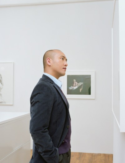 Man in art gallery facing picture, side view : Stock Photo